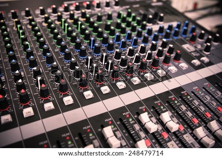 Hand on a Mixing Desk with vintage picture style, Music equipment in training room. - stock photo