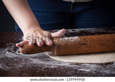 Hand on a rolling pin preparing pizza dough on a wooden table - stock photo