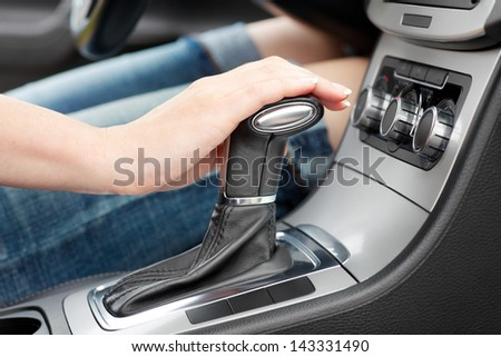 hand on automatic gear shift, woman in luxury car - stock photo
