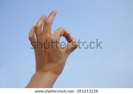 Hand on blue sky background .