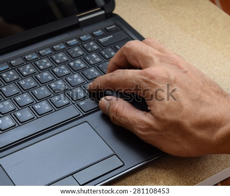 Hand on English-Thai keyboard layout of laptop