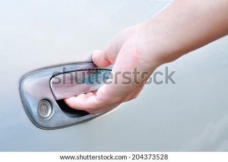 Hand on handle. Close-up of man in formalwear opening a car door for use as Illustration. - stock photo