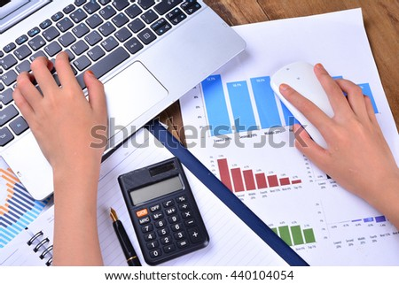 Hand on keyboard and mouse with graph, chart on wooden table - stock photo