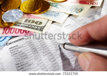 Hand on pen observing the foreign exchange data with money from different countries on edge - stock photo
