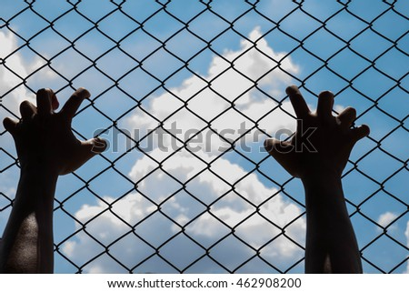 Hand on steel cage