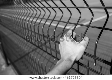 Hand on steel cage in back and white tone , concept of the freedom