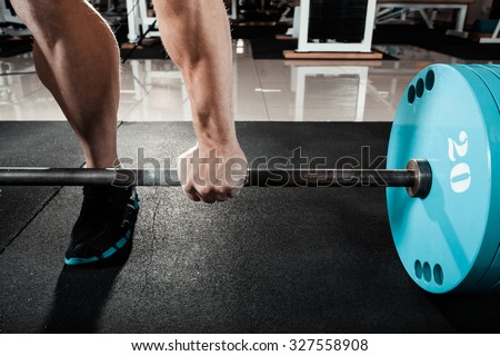 Hand on the barbell. Young athlete getting ready for weight lifting training - stock photo