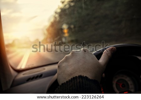 hand on the steering wheel - the driver drives into the sunset - stock photo
