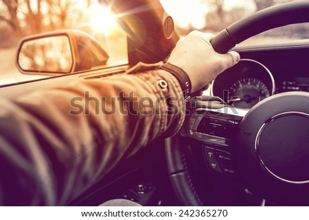 Hand on Wheel Car Driving.  Driving Modern Car Steering Wheel and the Hand Closeup. - stock photo