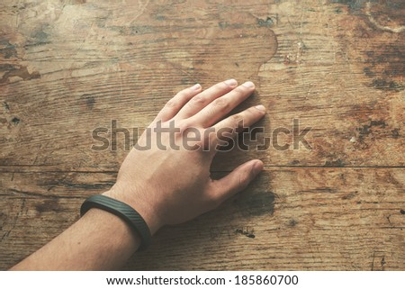 Hand on wood table wearing a fitness tracking armband - stock photo