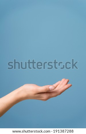 Hand Open. Adult woman's hand. Isolated on blue