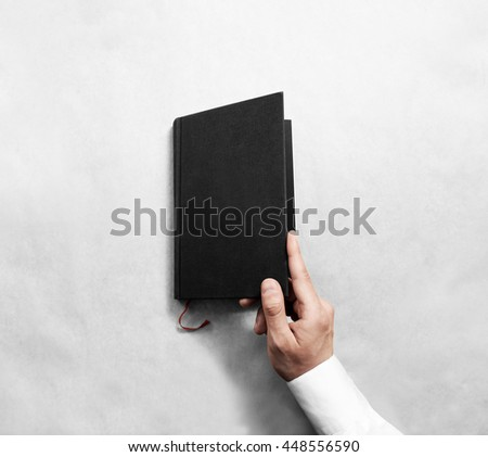 Hand open blank black book cover mock up template. Clear booklet surface design mockup. Arm holding opened textbook diary. Reading grey notebook copy. Closed catalog presentation display. - stock photo
