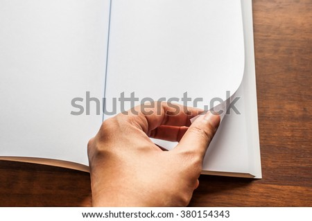 hand open blank book on  table