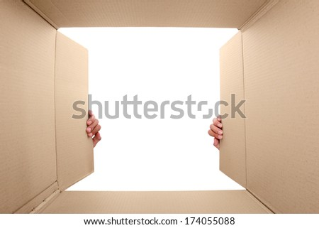hand open cardboard box. portrait from inside the box - stock photo