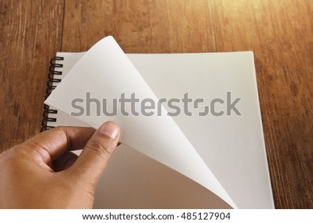 Hand open notebook on wood table