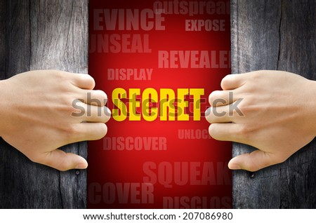 "Hand opening a wooden door and found the ""SECRET"" word in the middle of many different words on red background. - stock photo"