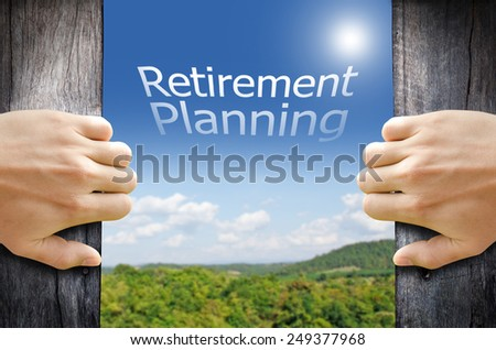 Hand opening a wooden door to a new world. Retirement Planning Concept. - stock photo
