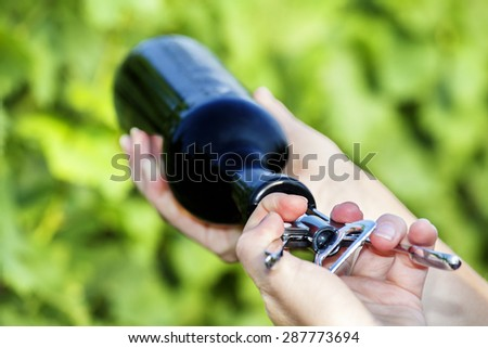Hand opening bottle of wine in the vineyard