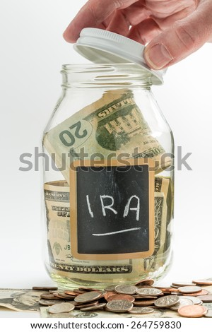 Hand opening lid of glass jar on white background with black chalk label and used for savings US dollar bills for IRA and retirement - stock photo