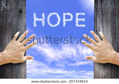"""Hand opening the wooden door and see """"HOPE"""" text cloud in the Sky. - stock photo"""
