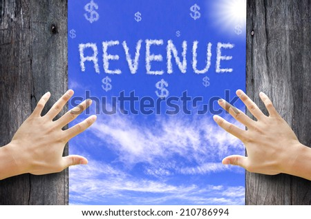 """Hand opening the wooden door and see """"REVENUE"""" text cloud in the Sky. - stock photo"""