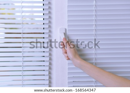 Hand opening window with white jalousie, close up