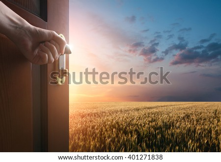 hand opens the door to the meadow with green grass and glue sky - stock photo