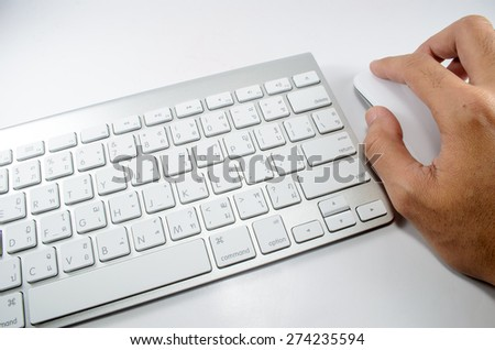 Hand operasting white mouse near white keyboard
