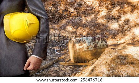 Hand or arm of engineer hold yellow plastic helmet for workers security on dry trash  hole in brown yellow toxic land with rusty old metal oil barrel and wooden board Ecology idea concept - stock photo