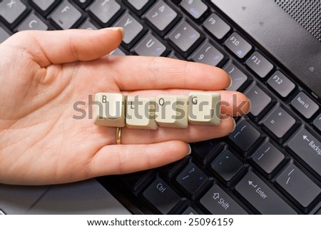 Hand over computer keyboard holding keys that spell blog - stock photo