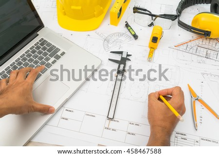 Hand over Construction plans with yellow helmet and drawing tools on blueprints - stock photo