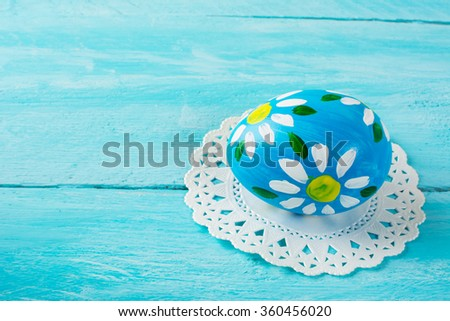 Hand-painted blue Easter egg with floral design on a blue wood plank background. Easter background. Easter symbol. Copy space - stock photo