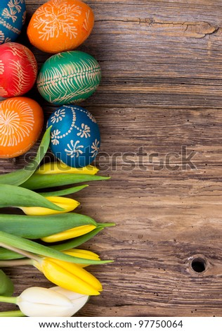 Hand-painted easter eggs with tulips  on wooden background - stock photo