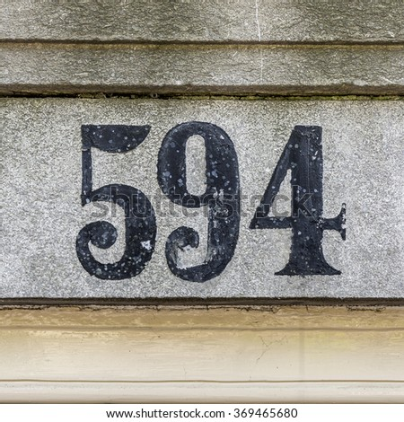 Hand painted house number five hundred and ninety four. - stock photo
