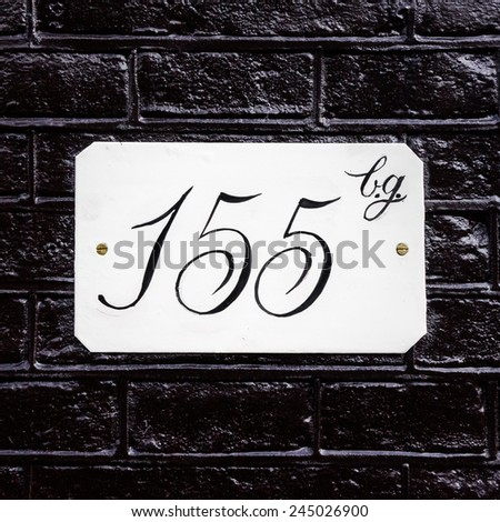 hand painted house number one hundred and fifty five - stock photo