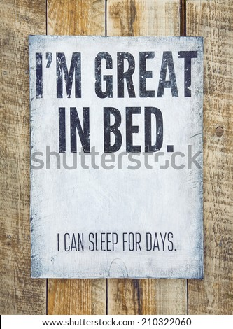 """Hand-painted motivational  retro poster on the rustic wooden background saying """"i'm great in bed, i can sleep for days"""". Home decoration. - stock photo"""