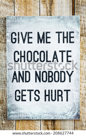 """hand-painted motivational wooden vintage board on the rustic wooden background saying """"Give me the chocolate and nobody gets hurt"""" - stock photo"""