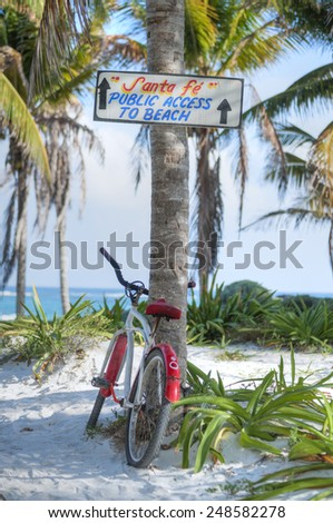 Hand-painted wooden sign on coconut palm directs visitors to Santa Fe public beach in Tulum, Mexico while a bicycle leans against palm tree - stock photo