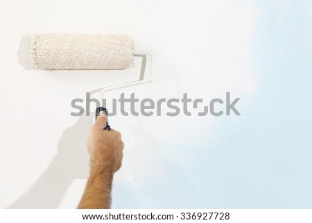 hand painter man at work with a paint roller, wall painting concept - stock photo