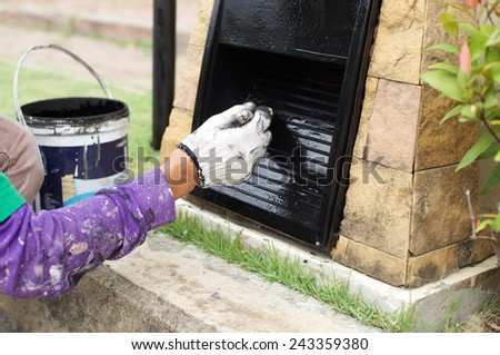 hand painting a electric post in black color with a paintbrush - stock photo