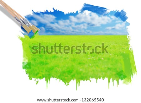 Hand painting beautiful green grass against a blue sunny sky