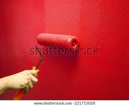 Hand Painting Red Color on The Wall - stock photo