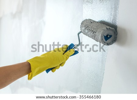 Hand painting wall in grey - stock photo
