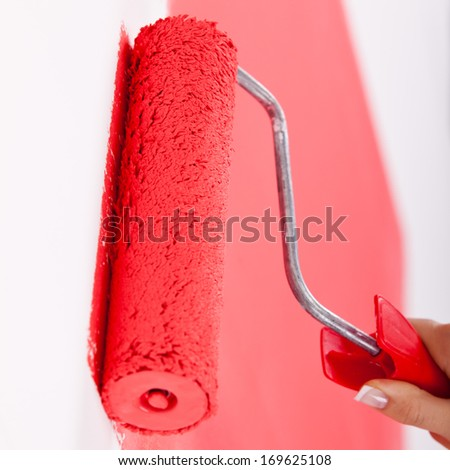 Hand painting wall in red - stock photo
