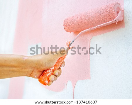Hand painting white wall with paint roller