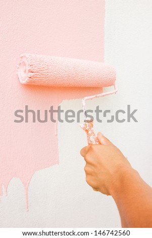 Hand painting white wall with paint roller - stock photo