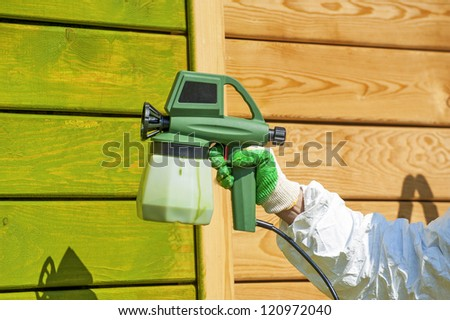 Hand painting wooden wall with spray gun in green - stock photo