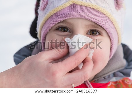 Hand parent helping her child to blow his nose.