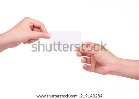 Hand passing a card. Man and woman hands passing each other a business card  - stock photo