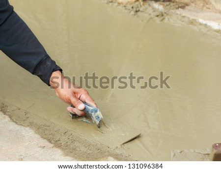 hand pastering cement mortal on the floor - stock photo